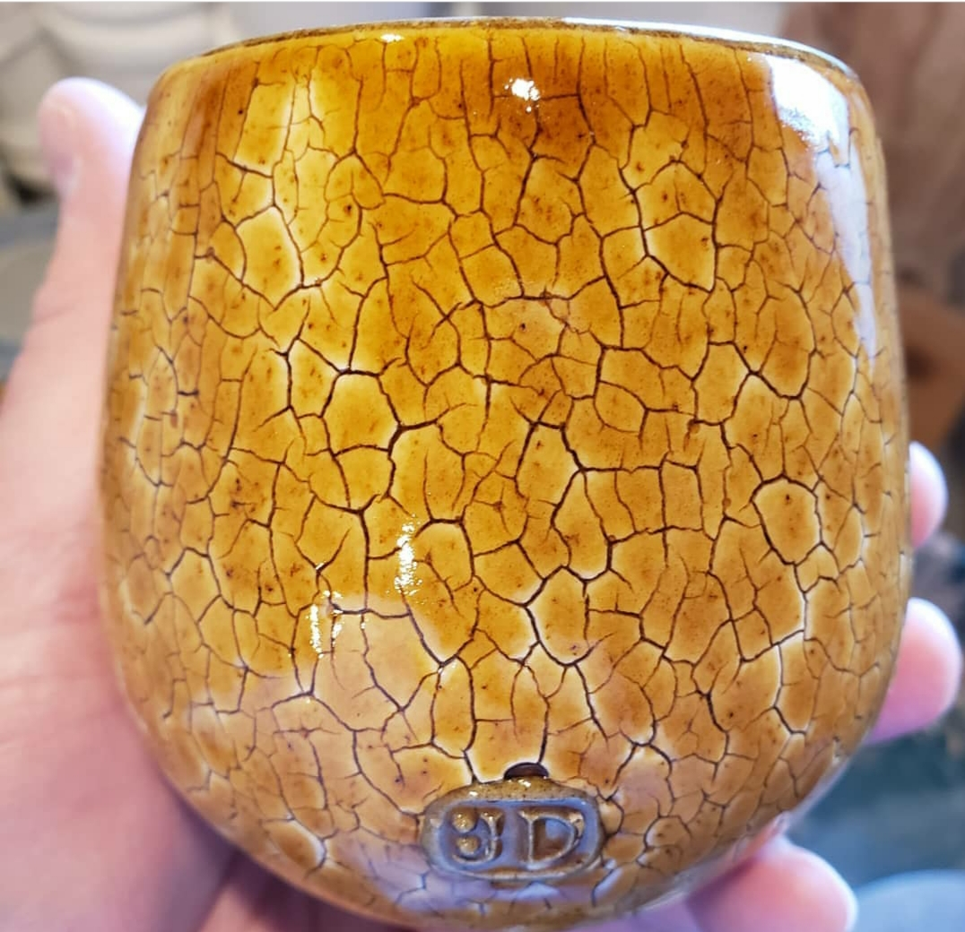 A pottery mug with a honey over-glaze that highlights an engobe having a decorative crack pattern