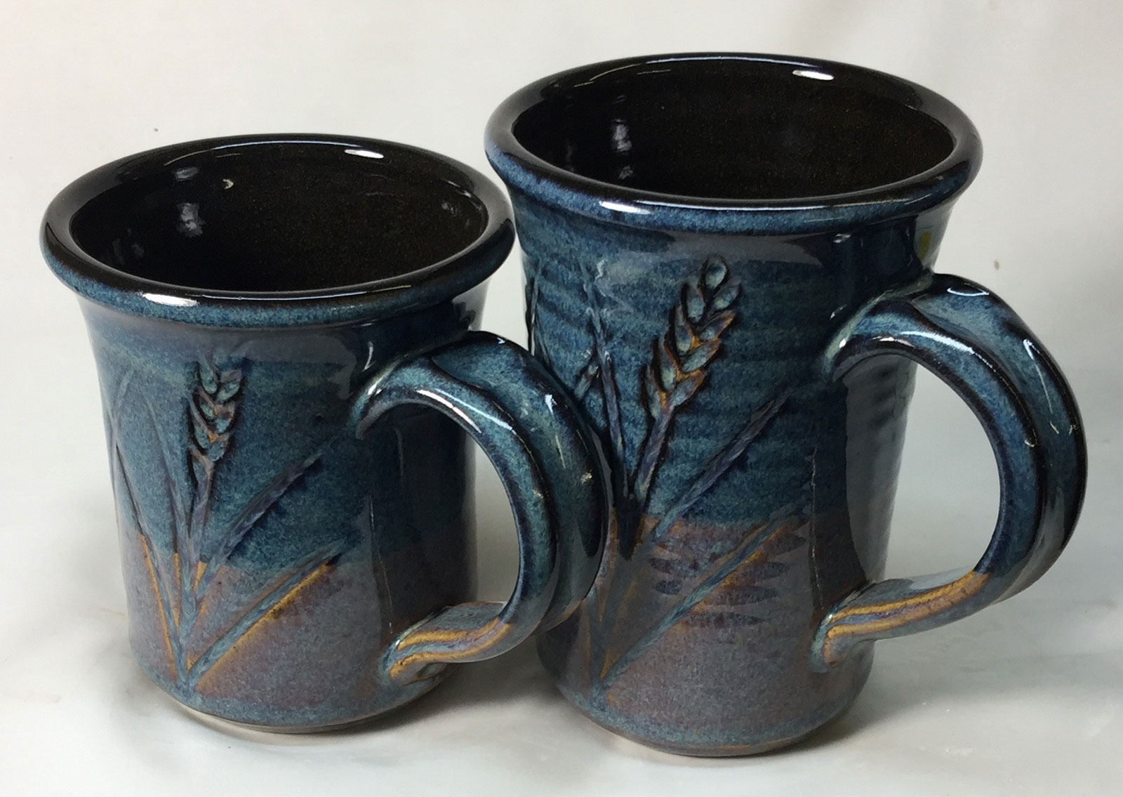 A black engobe transforms the floating blue glaze over it